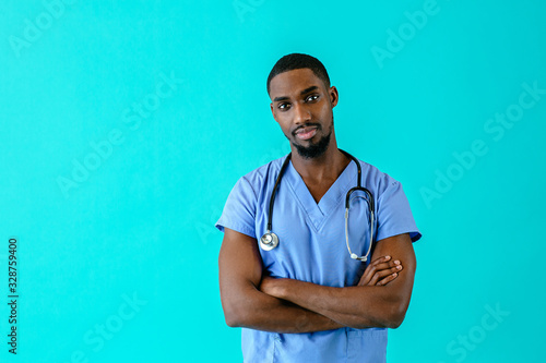 Portrait of a serious male doctor or nurse wearing blue scrubs uniform and stethoscope with arms crossed, isolated on blue background