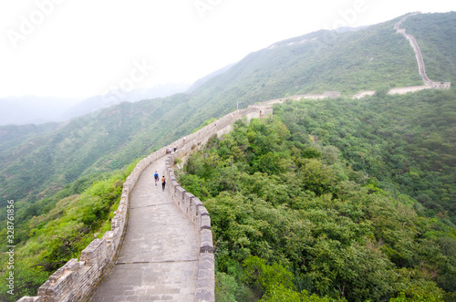 A view along the Great Wall of China, with a few tourists, and the surrounding hills covered by low cloud Fototapeta