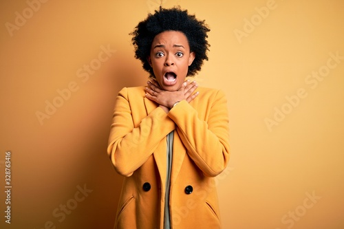 Young beautiful African American afro businesswoman with curly hair wearing yellow jacket shouting and suffocate because painful strangle Wallpaper Mural