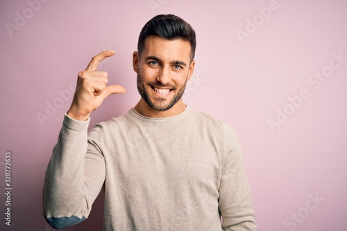 Photo Young handsome man wearing casual sweater standing over isolated pink background smiling and confident gesturing with hand doing small size sign with fingers looking and the camera