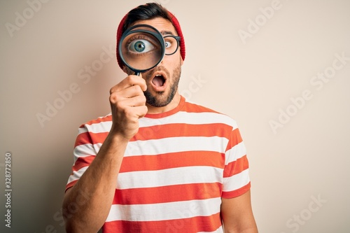 Photo Young detective man looking through magnifying glass over isolated background sc