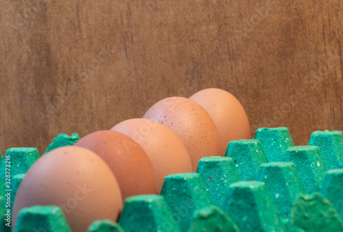 Eggs in a row on a green cardboard made with recycled paper, close up Wallpaper Mural