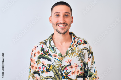 Young handsome man wearing Hawaiian summer shirt over isolated background with a happy and cool smile on face. Lucky person.