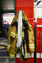 A Firefighters Coat Hanging On The Outside Of A Fire Engine.
