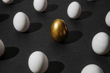 White And Gold Chicken Eggs In Vertical Position On Plain Black Paper Background. Creative Minimalist Abstract Easter Concept.