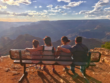 Family Of Four Watching The Sunset On A Bench At Desert View Watchtower In The Grand Canyon National Park, UNESCO World Heritage Site, Arizona