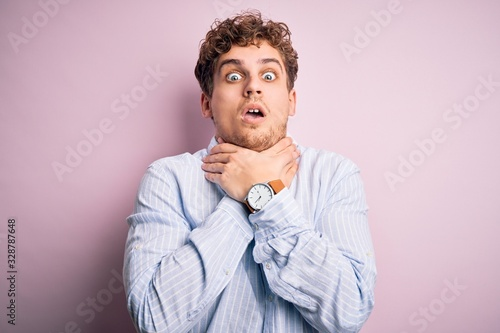 Photo Young blond handsome man with curly hair wearing striped shirt over white background shouting suffocate because painful strangle