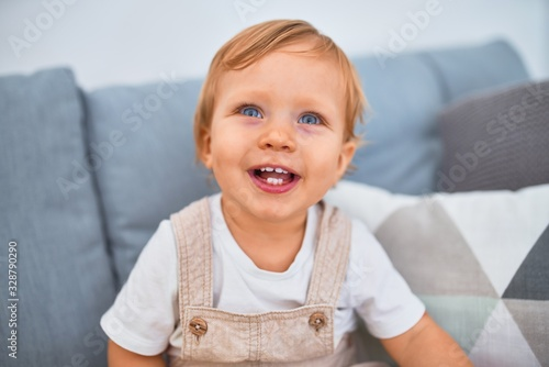 Photo Adorable blonde toddler sitting on the sofa smiling happy at home