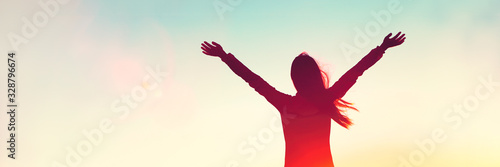 Fototapeta Happy woman sihouette with arms raised up in success on sunset glow sunshine banner panorama. Wellness, financial freedom, healthy life concept background. obraz