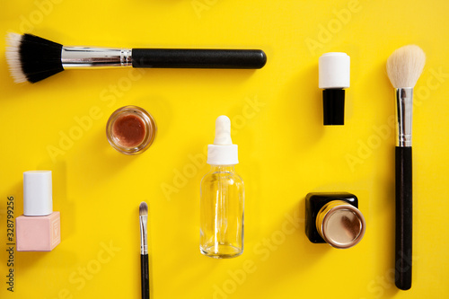 make up flat lay on yellow background, cosmetics knolling. White, black and pink cosmetic accessories.