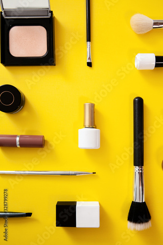Make up flat lay knolling - make up artist accessories on yellow background