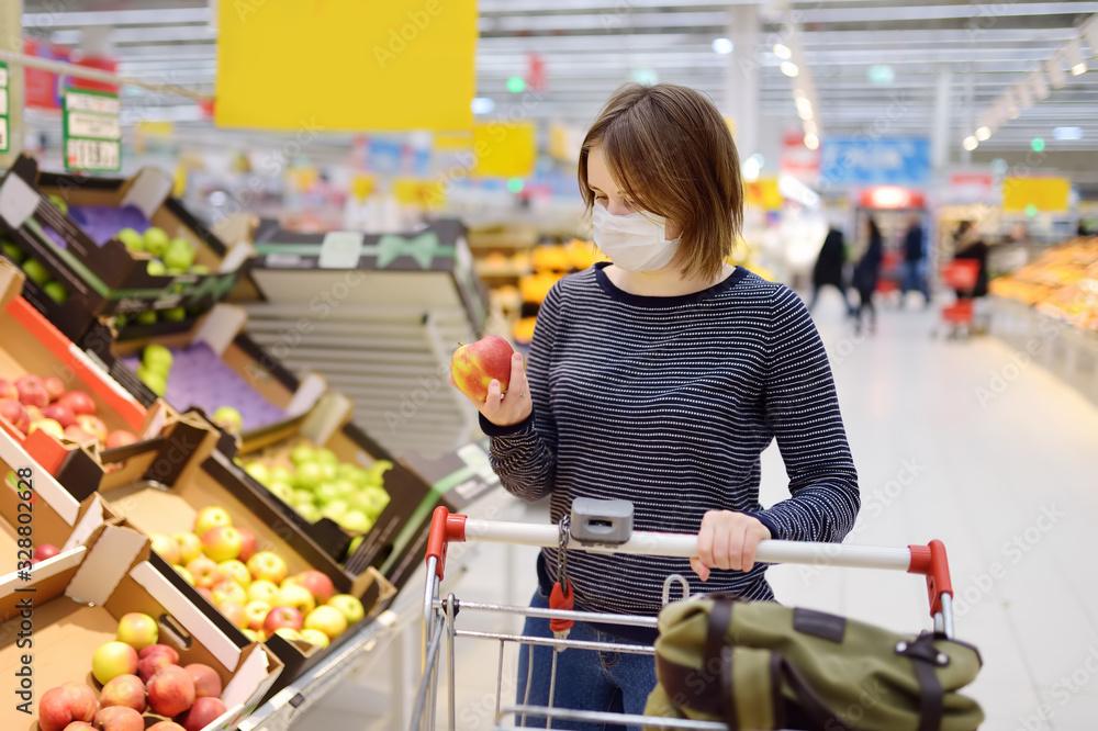 Fototapeta Young woman wearing disposable medical mask shopping in supermarket during coronavirus pneumonia outbreak