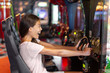 Arcade game machine adult woman having fun playing racing car videogame driving virtual sports cars.