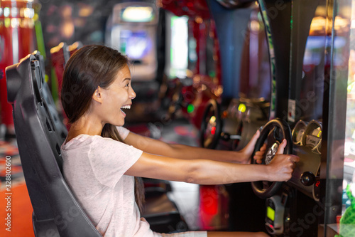 Arcade game machine adult woman having fun playing racing car videogame driving virtual sports cars Wallpaper Mural
