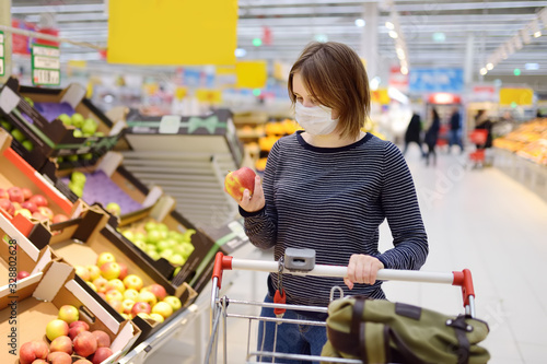 Young woman wearing disposable medical mask shopping in supermarket during coronavirus pneumonia outbreak