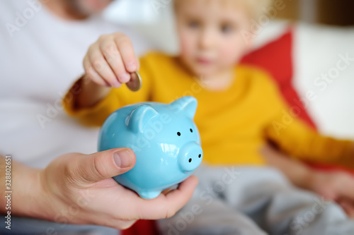 Father and child putting coin into piggy bank Fototapete