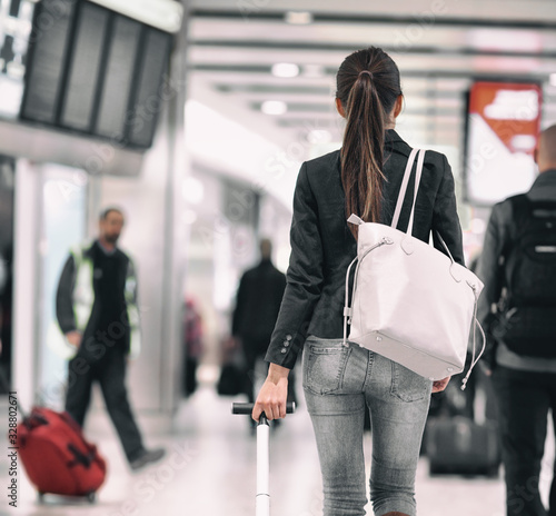 fototapeta na szkło Travel background airport terminal passengers walking in lounge. Asian woman walking from behind with purse carrying luggages for delayed flights to vacation holidays.