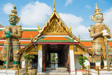 View Of Bright Colored And Gold Decorated Gates With Two Mythical Demon Guardians. Grand Palace, Bangkok, Thailand