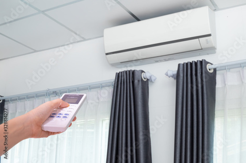 Hand pressing remote control air conditioner in room. Canvas Print
