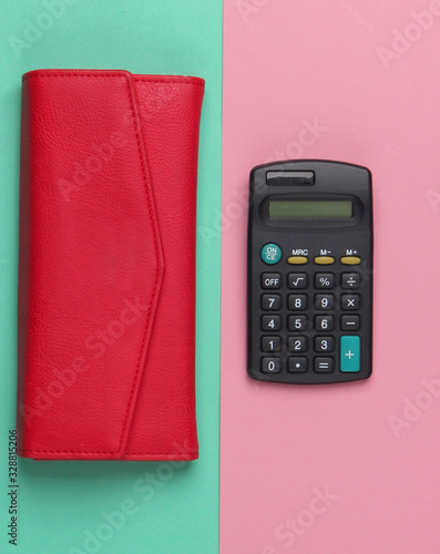 Calculator with a leather wallet on a blue-pink pastel background. Family bujet, economical calculation, additional accounts of expenses. Top view - 328815206
