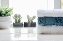 Stack Of Clean Towels And Houseplant On White Wooden Table.