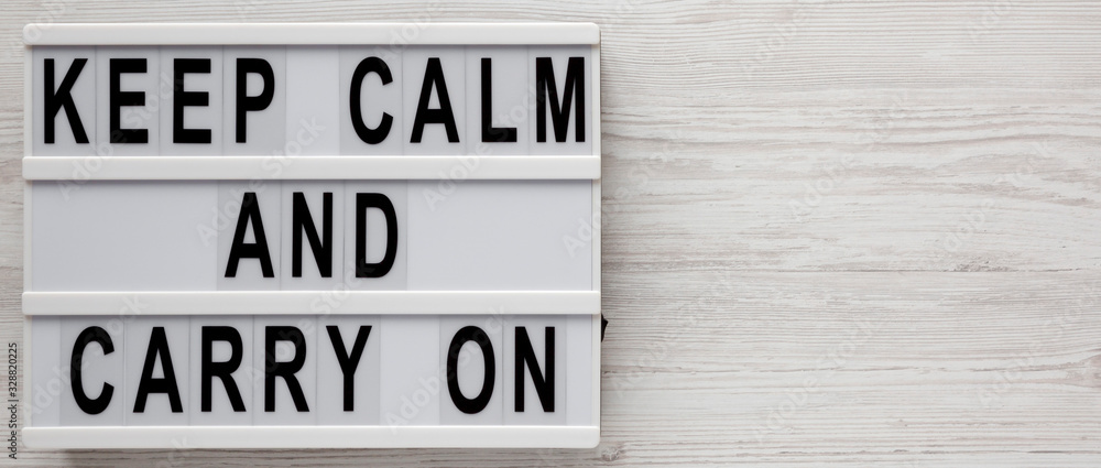 Fototapeta 'Keep calm and carry on' words on a lightbox on a white wooden background, top view. Overhead, from above, flat lay. Copy space.