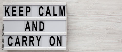 Fototapeta 'Keep calm and carry on' words on a lightbox on a white wooden background, top view. Overhead, from above, flat lay. Copy space. obraz