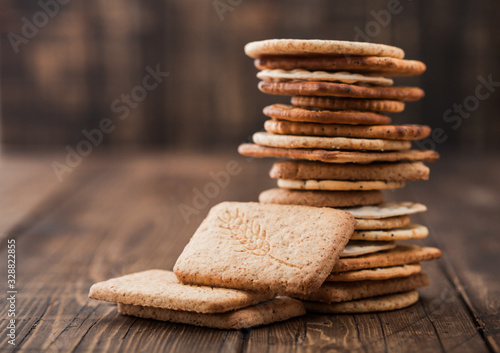 Photo Stack of various organic crispy wheat, rye and corn flatbread crackers with sesame and salt on wooden background