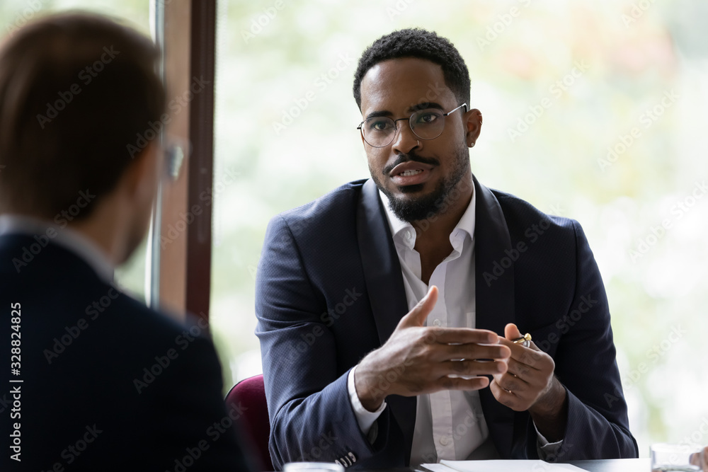 Fototapeta Confident concentrated African American male employee talk with colleague explain thought or idea, focused biracial businessman speak with coworker or partner, brainstorm at office boardroom meeting