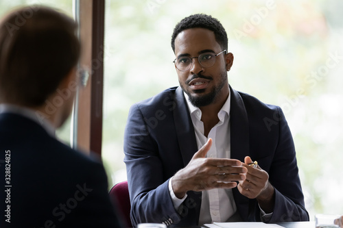 Confident concentrated African American male employee talk with colleague explai Canvas Print