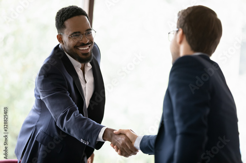 Photo Smiling diverse male business partners shake hands get acquainted greeting at of