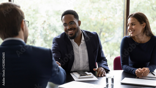 Photo Smiling African American male employee shake hand of colleague greeting getting