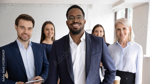 Group portrait of smiling motivated multiracial businesspeople stand show unity Wallpaper Mural