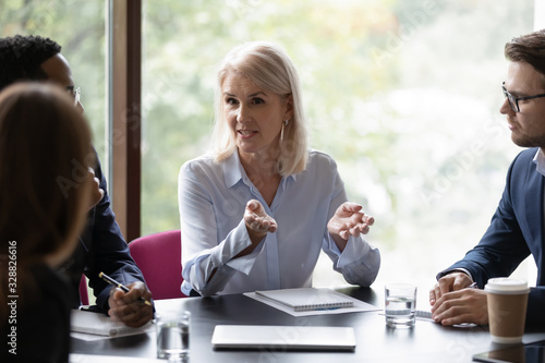 Fototapeta Confident focused middle-aged businesswoman head team meeting with diverse colleagues, consider paperwork together, concentrated female boss talk brainstorm discuss business project with coworkers obraz