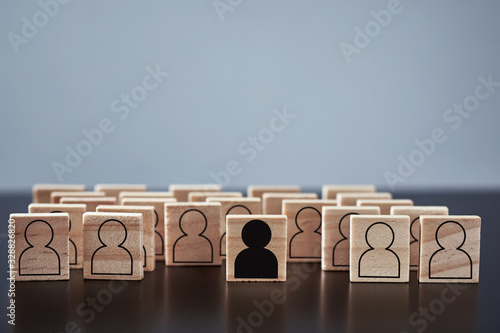 Fototapeta Concept of racism and misunderstanding between people, prejudice and discrimination. Wooden block with a white people figures and one with black man obraz