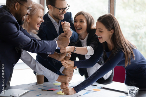 Fototapeta Overjoyed diverse businesspeople stack fist engaged in funny teambuilding activity at office meeting together, happy motivated multiracial employees join hands show unity and support, teamwork concept obraz