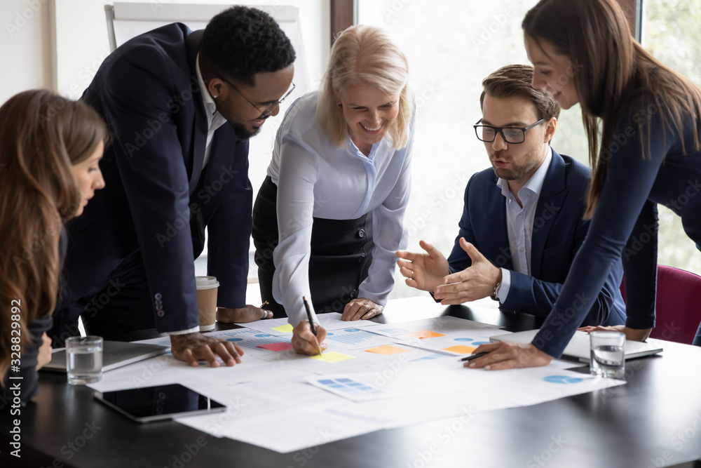 Fototapeta Happy motivated diverse businesspeople work together cooperate at business office meeting, smiling multiracial colleagues discuss ideas financial project at boardroom briefing, collaboration concept