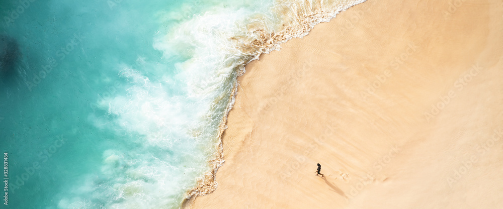 Fototapeta View from above, stunning aerial view of a person walking on a beautiful beach bathed by a turquoise sea during sunset. Kelingking beach, Nusa Penida, Indonesia.