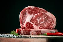 Raw Rib Eye Beef Steak On A Bl...