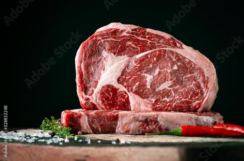 Fotografia Raw rib eye beef steak on a black background