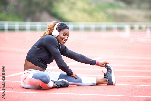 black runner woman is stretching