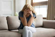 Upset Young Woman Sit On Couch...
