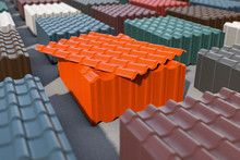 Stacks Of Metal Tile Sheets Of Different Colors In The Warehouse For Roof Construction.