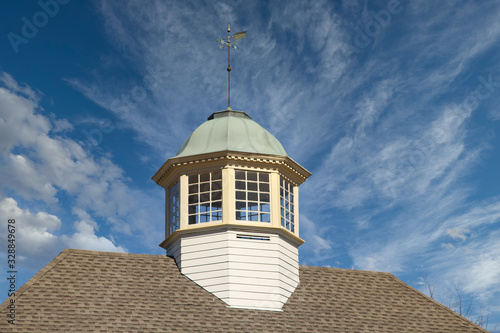 Roof line of a building with wood and copper cupola and weather vane against a c Fotobehang