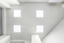Cassette Suspended Ceiling With Square Halogen Spots Lamps And Drywall Construction In Empty Room In Apartment Or House. Stretch Ceiling White And Complex Shape. Looking Up View