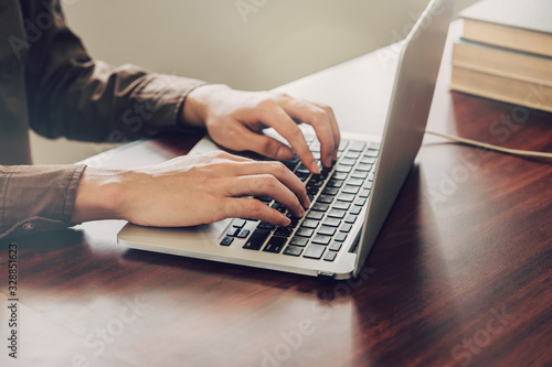 business man hand texting laptop on wooden table