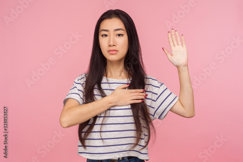 I give you promise! Portrait of responsible, honest girl with brunette hair keeping hand on chest and raising palm to take oath, pledging allegiance Canvas Print
