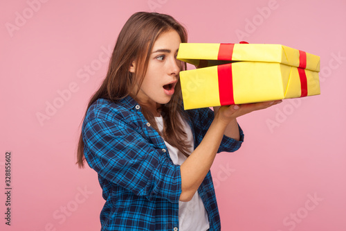 Valokuva Portrait of curious amazed girl in checkered shirt looking inside present box with astonished shocked expression, pleasantly surprised by birthday gift