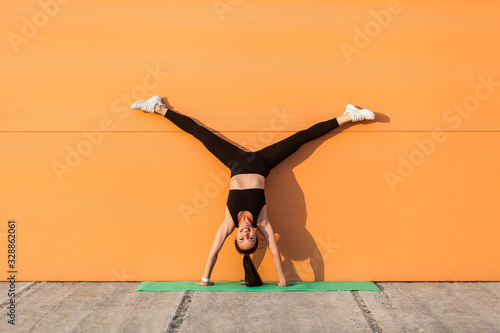 Obraz na płótnie Glad happy humorous girl with perfect athletic body in tight sportswear doing yoga handstand pose with spread legs against wall and showing tongue, having fun