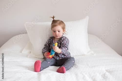 Horizontal portrait of adorable fair toddler girl in grey top and leggings sitti Tapéta, Fotótapéta